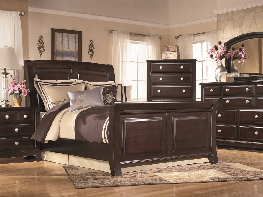 Dark brown wooden furniture set in a bedroom.