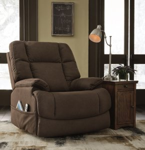 The Fourche power recliner with luxurious padding, one-touch power reclining and power lumbar. Next to is ia a side table with a cabinet and a lamp on top.