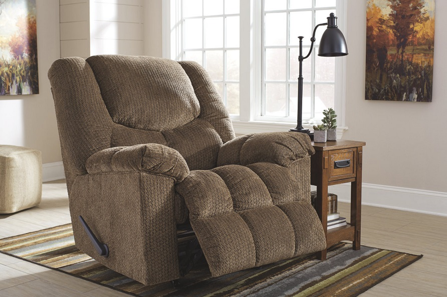 The Brownstone Turboprop recliner on a striped rug with a small side table next to the recliner. There is a lamp on the side table and a painting on the wall of trees.