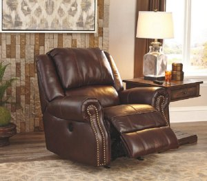 The Chestnut Collinsville leather recliner with a nailhead trim. next to a brown wooden side table with a lamp on it.