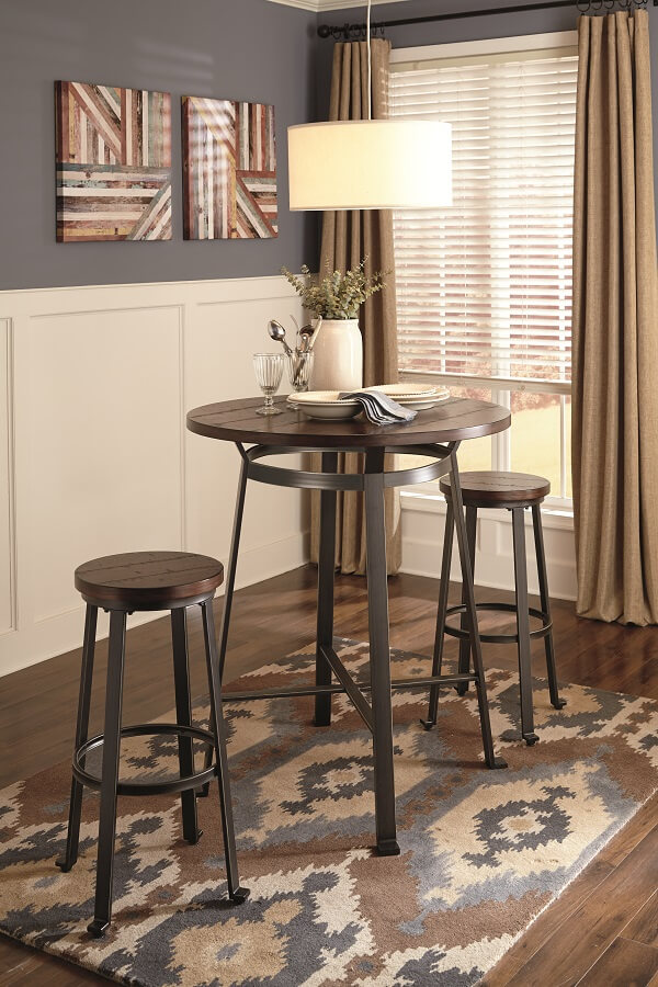 A brown pub styled table with bar stools and a abstract tug underneath