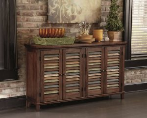 A rustic wooden server with colorful stripes on the cabinet doors in front of a brick wall with decor accents on top of the server.