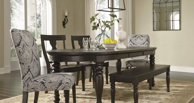 large oval dining table with a complementing mix of solid wood chairs and bench accented with blue upholstered chairs