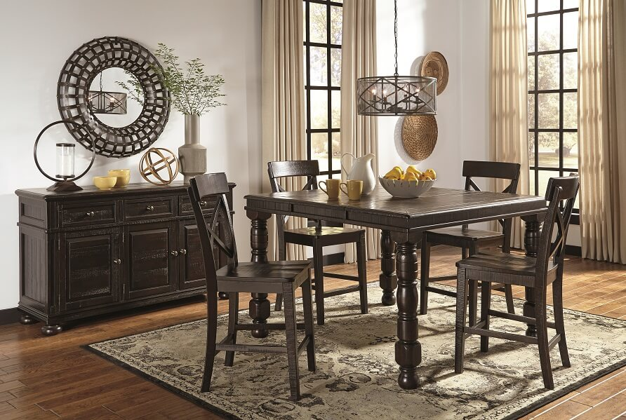 dark brown rectangle kitchen table and bar chairs with a server against the wall and a rug under the table.