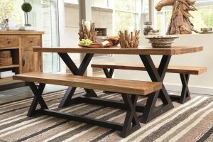 Wooden dining table with wooden benches on top of a striped area rug.