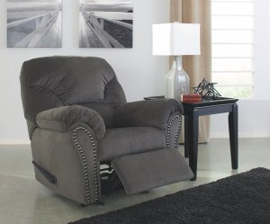 Gray kinlock recliner with nailhead accecents next to a side table with a lamp. Above recliner is a wall canvas of a dock overlooking the water.