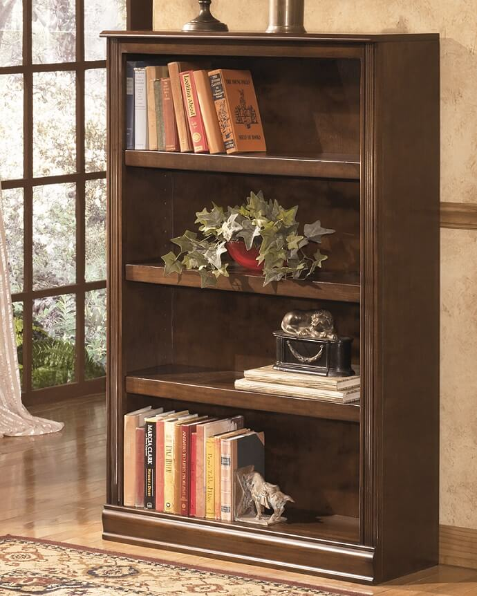 Small bookcase against a wall holding many books, a plant and 2 sculptures.