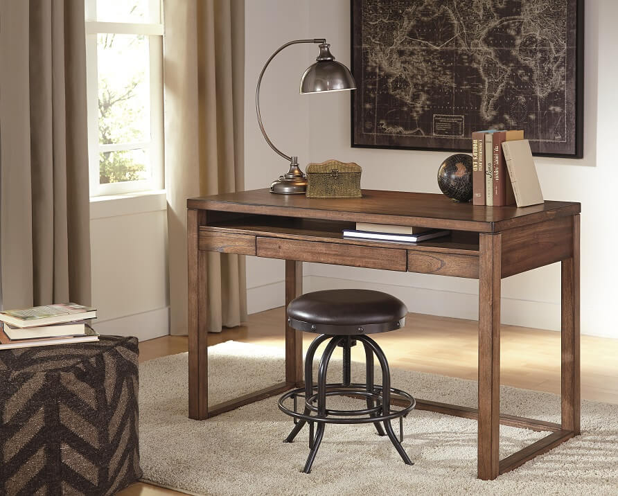 Plain brown wooden desk with leather stool and a black map on the wall.