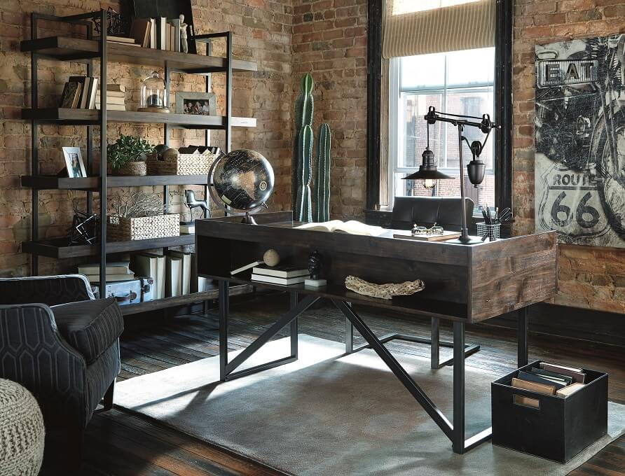 Urban designed office setting with a desk and a bookcase on one will topped with industrial sculptures such as globes, lamps and sculptures.