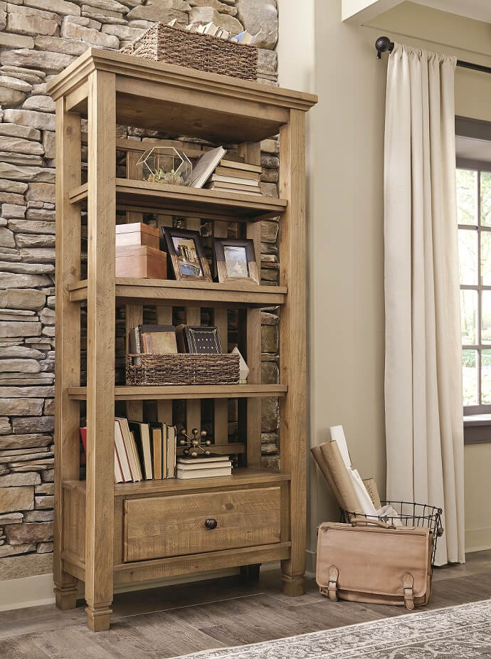 light brown wood open faced bookcase with four shelves and storage drawer holding magazines and books and other keepsakes.