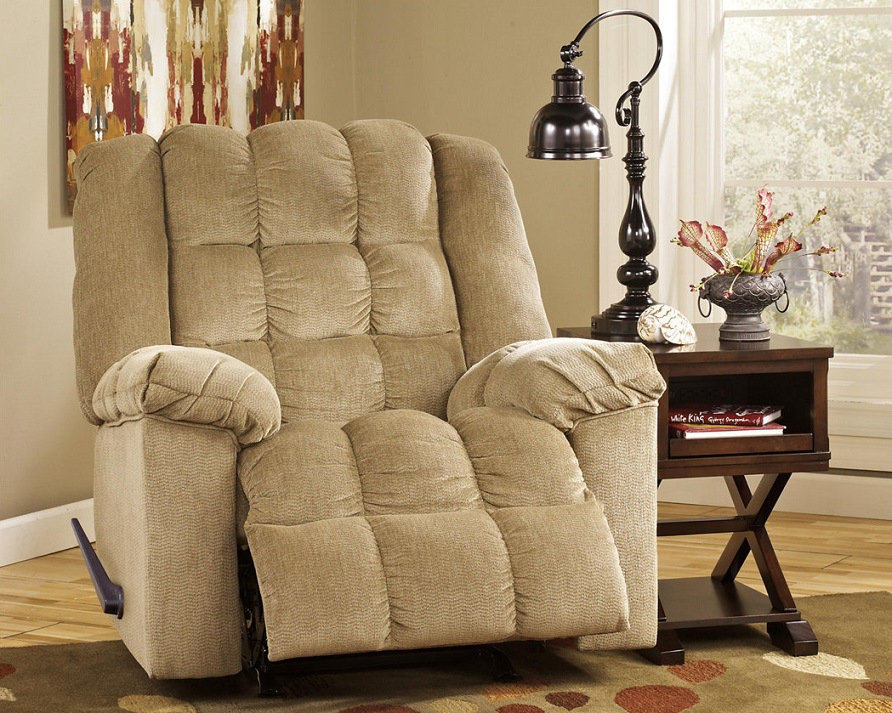 The sand Colored Ludden recliner with lots of plush next to a side table with storage space. A lamp is on top of the side table and there is abstract wall are behind the recliner.