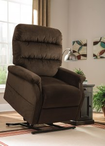 The brown Brenyth Power Lift recliner in lifted position on a creme colored rug in an empty room with windows and a side table next to the recliner.