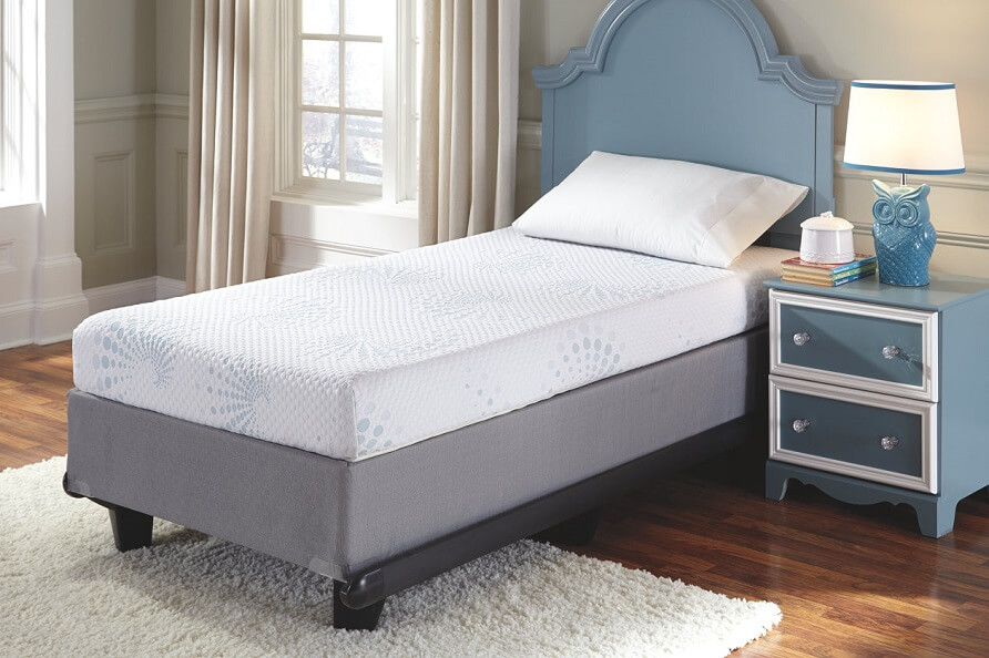 twin mattress in an empty kids room with a nightstand and owl lamp on the top.