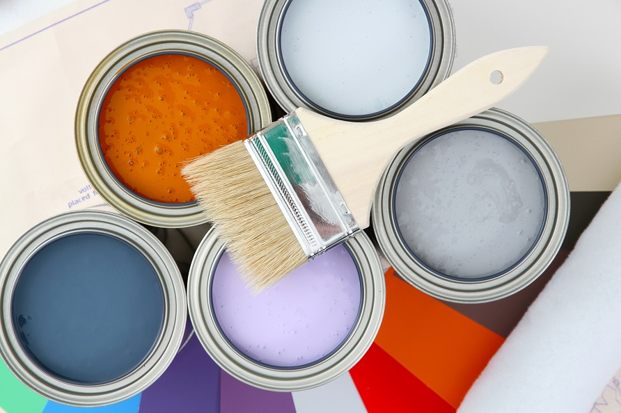 Paint cans of different colors ready to be used on white background