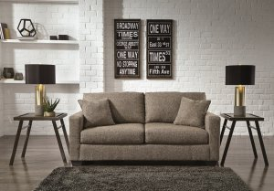 Ash colored sofa in a plain white room with a white brick wall and gray rug on the floor with two modern side table next to it.