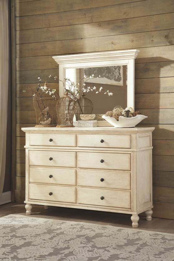 White rustic dresser with a mirror in front of wood paneling with a farmhouse chic rug in front.