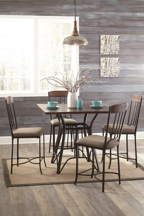 Dining room table in an open room with 4 chairs, the table is set and a tan rug is underneath.