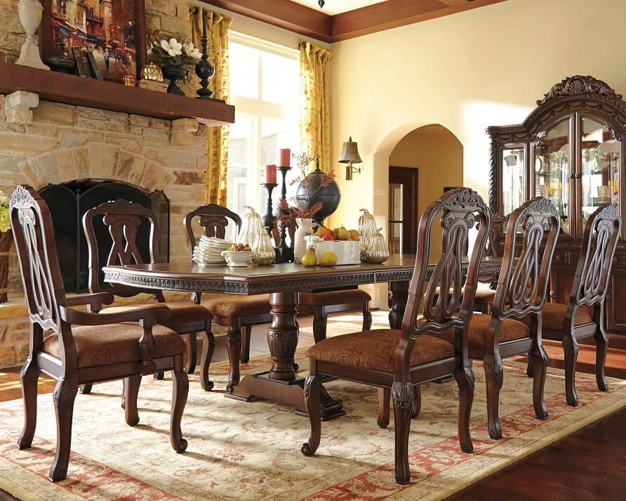 Long rectangular dining table with elegant flair with dining chairs with engravings on them.