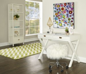 White and modern writing desk with gold nobs and a shaggy stool underneath the desk.