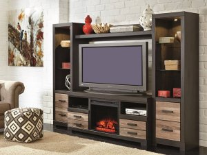 Black entertainment center staged with home decor pieces with drawers along the bottom in a room with a rug and a pouf