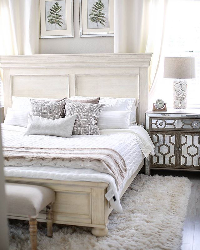 Comfortable memory foam mattress with white bedding on top as well as plush blanket underneath and nightstand on the side.