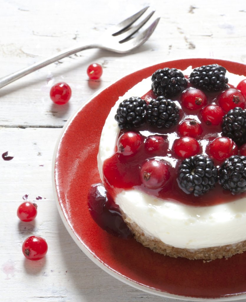 mini cheesecake with red fruits on plate on rustic background