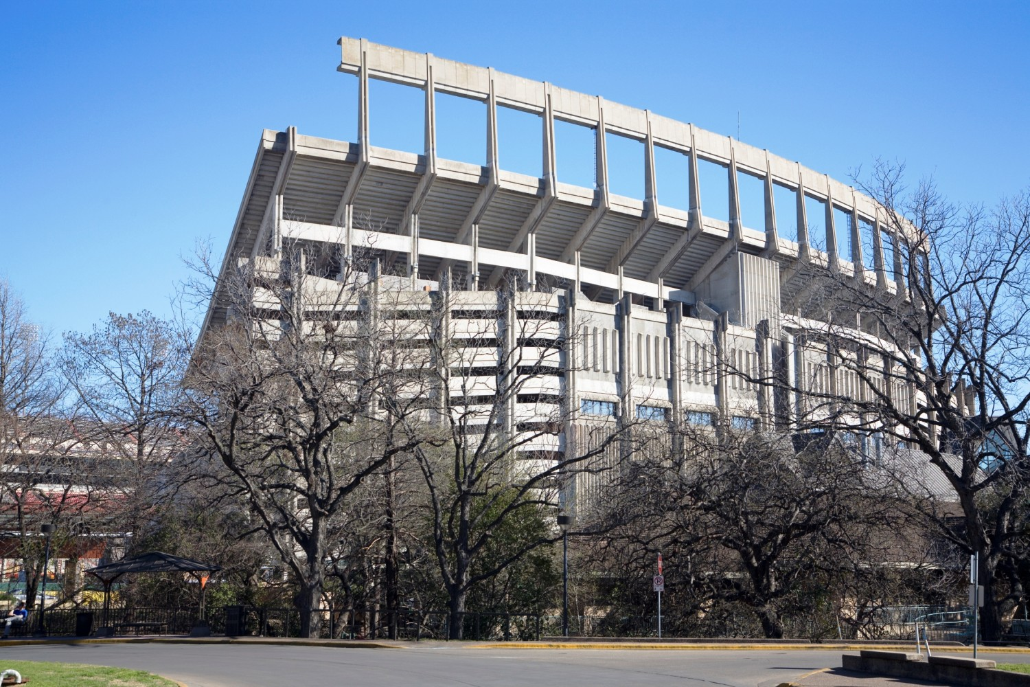 This photo was taken in late February, well before the trees began to leaf out - which allow the viewer to see through the trees.  In the lower ldeft portion of the photo, it should be noted that the north endzone seating has been demolished, and the University of Texas is preparing to add two levels of seating there, complete with clubhouses. This photo was taken from the East Mall fountain, and the Texas Exes Alumni Center is seen to the lower right.