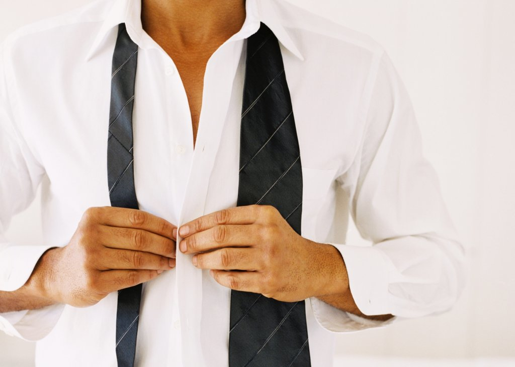 close-up of a man's hands buttoning a shirt