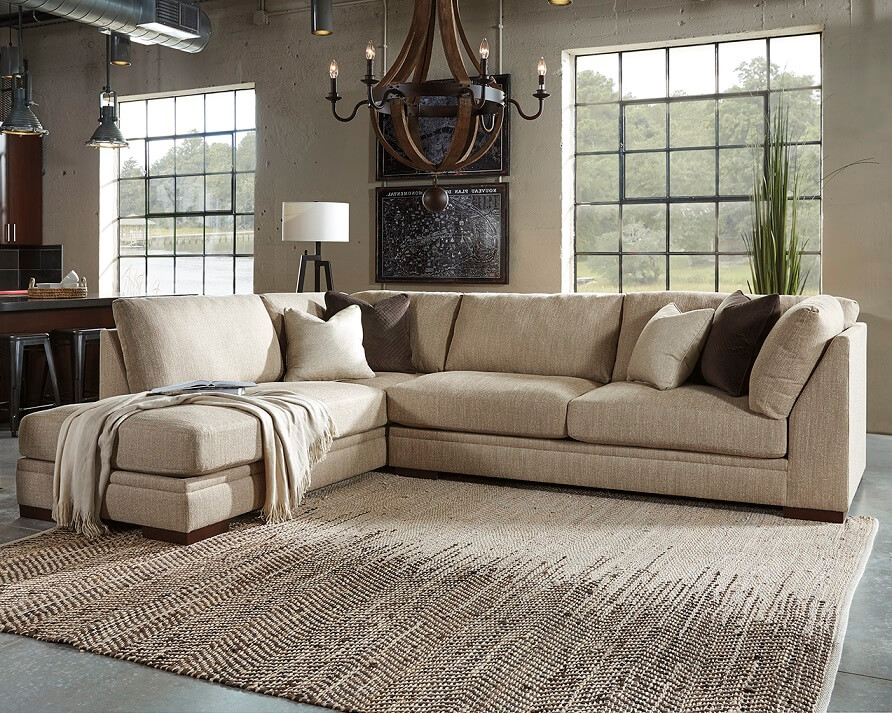 Large cream sectional with throw blankets draped on one side and a neutral rug in the middle with a chandelier above.