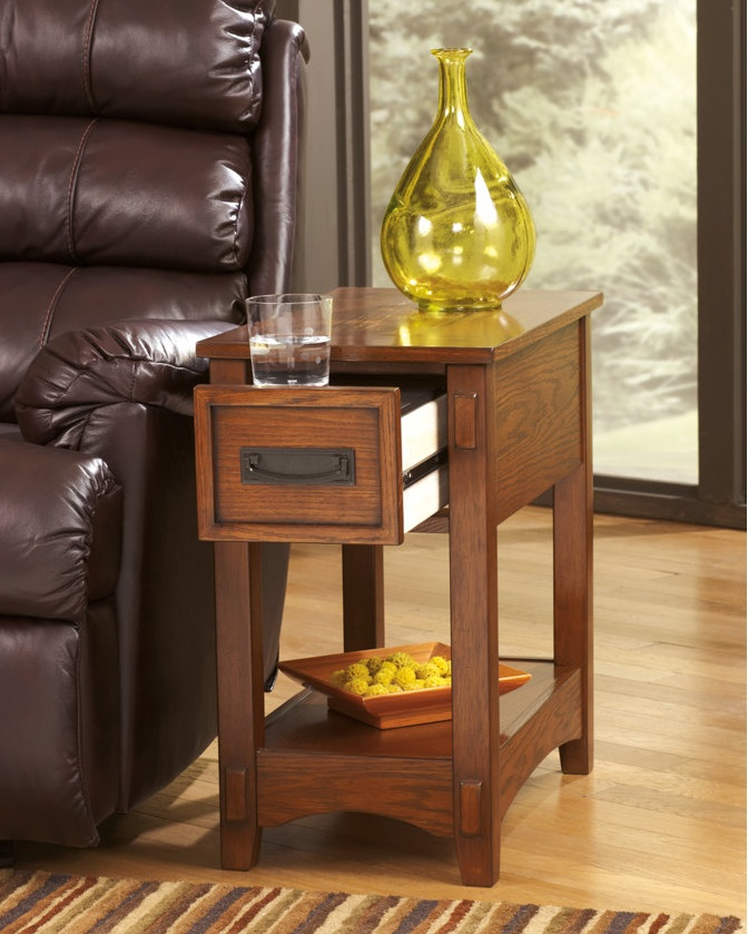 Small end table with a drawer that is holding a glass of water.