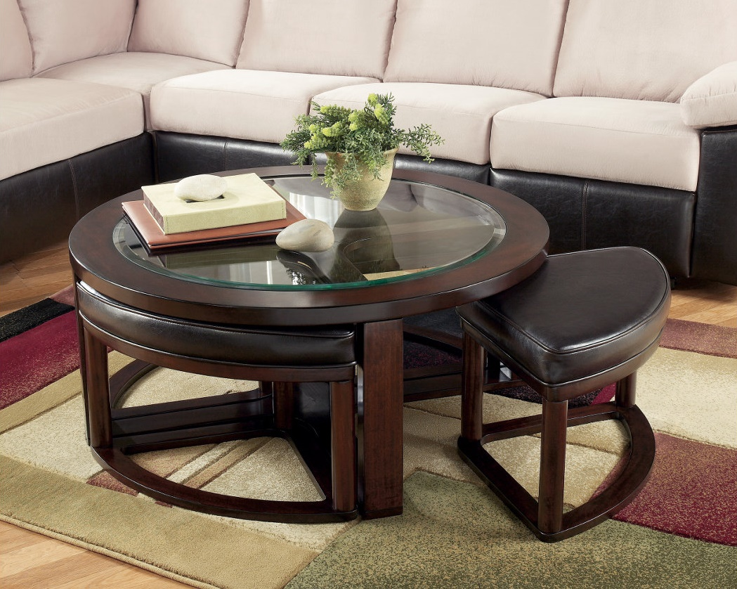 Small circular coffee table with a pull away seating in front of a white sectional.