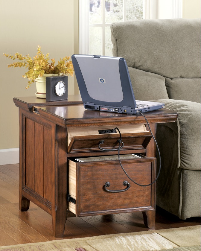 End table with functional features such as extra outlets for chargers. There's a laptop on top of the table as well as a clock and plant.