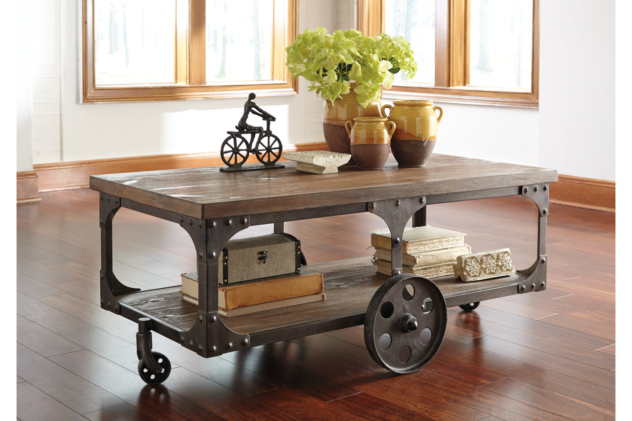 Brown industrial coffee table with wheels as legs with vases as decor on top.