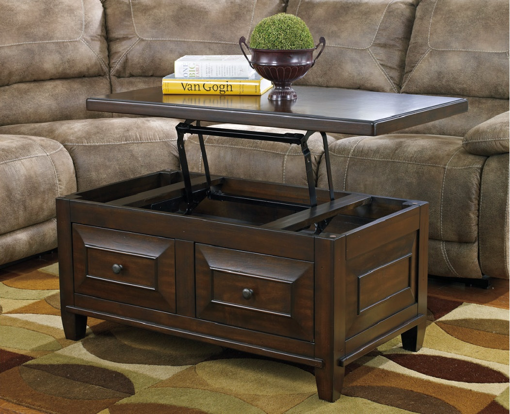 Dark brown table with lift top up with books and a succulent on top in front of a sectional