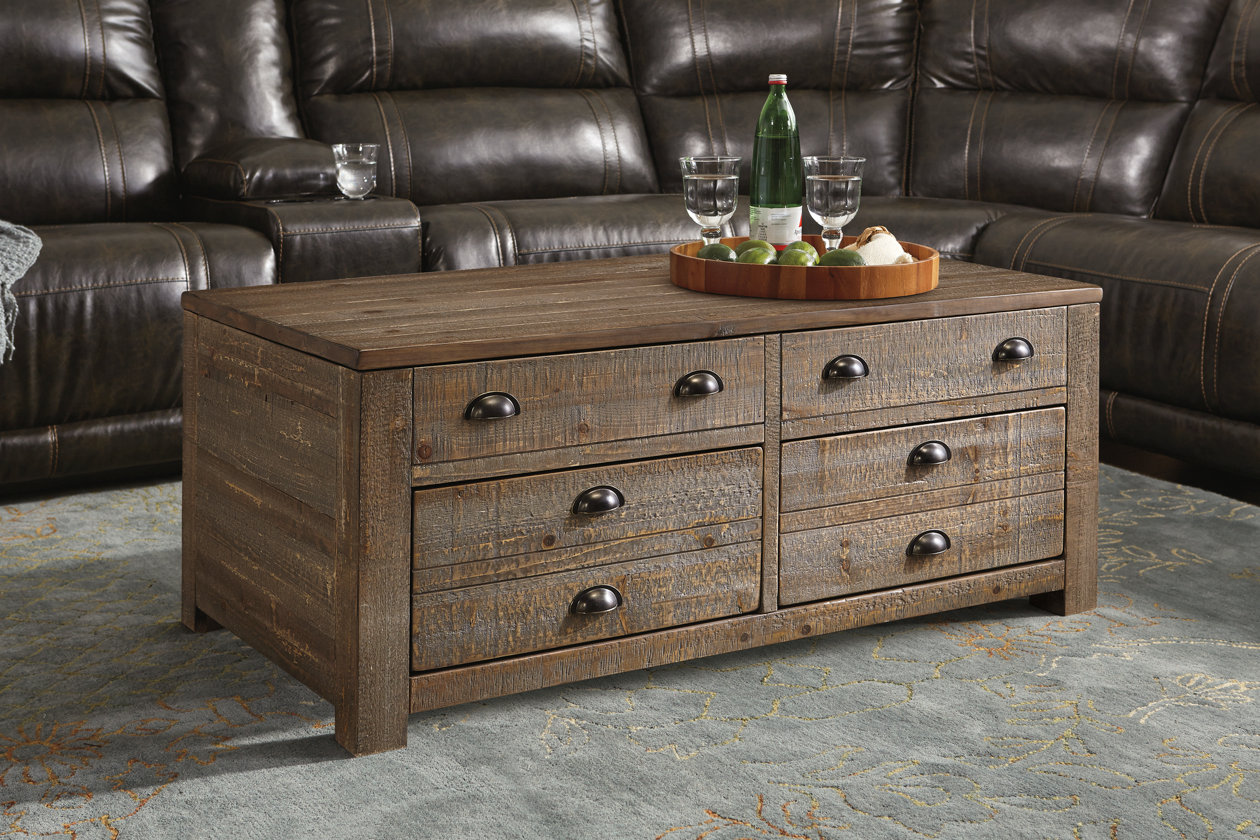Brown wooden coffee table with several drawers for storage with a serving tray on top in front of a brown leather sectional.
