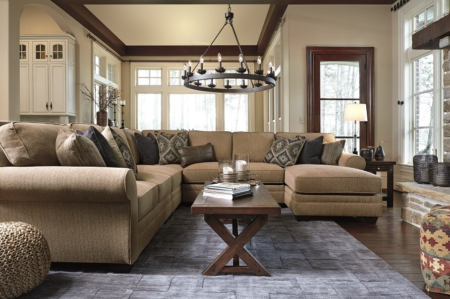 Ultra plush cushions and traditional styling, this sectional is cozy and classic. It is in a large living room setting with a blue rug and chandelier hanging above.