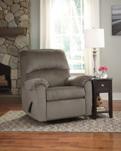 gray recliner in a room with one window and side table with a lamp on it.