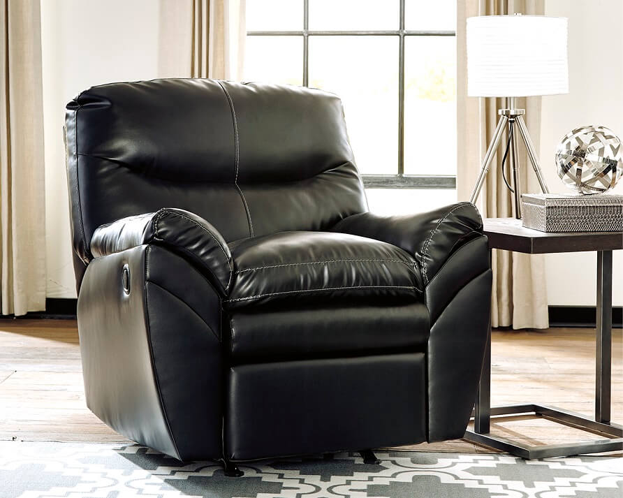 Black faux leather recliner in a room with one window and a side table next to the chair with a lamp on it.
