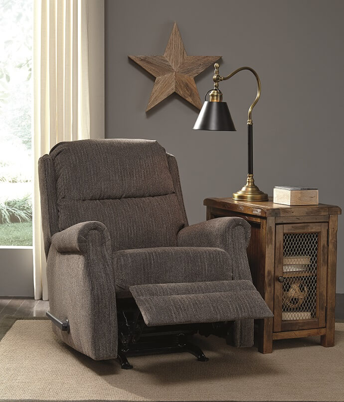 Reclining chair with gray fabric construction in a room with a rustic star on the wall with a wooden side table on the side of the recliner.