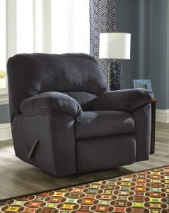 blue recliner in a room with one window and a side table with a lamp on it.