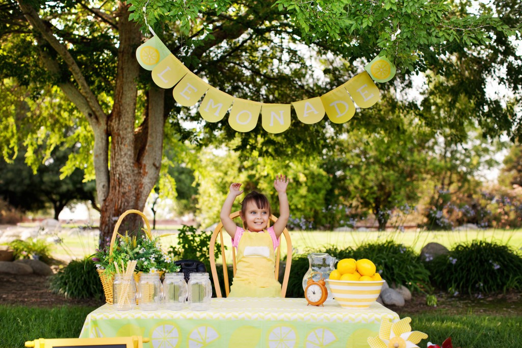 Little Girl At The Lemonade Stand Raising Hands