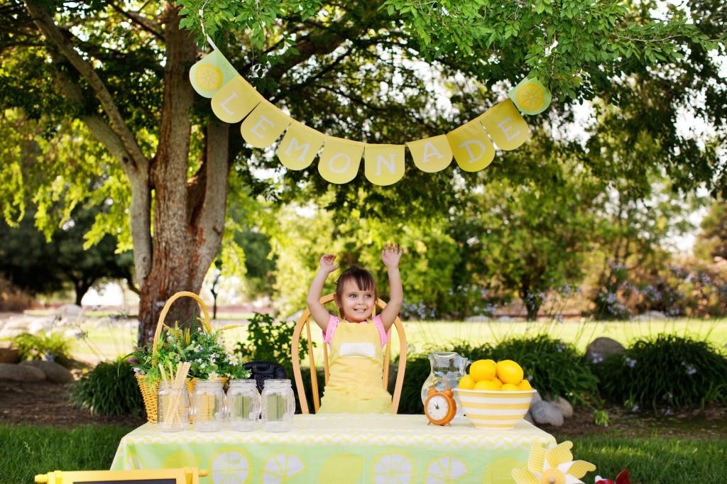Little Girl At The Lemonade Stand Raising Hands