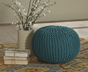 turquoise cable knit round pouf on a rug next to white flowers and white books