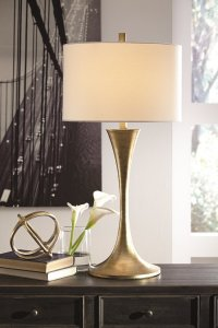 Gold metal table lamp with beige shade on a table.