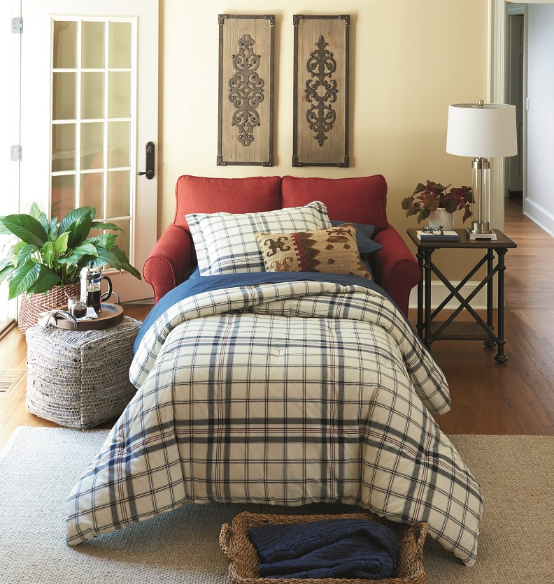 Red fabric sleeper sofa pulled out with a duvet cover and pouf next to it with a tray.