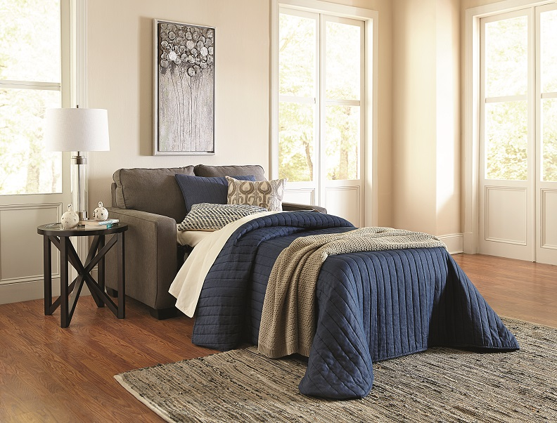Brown fabric sleeper sofa pulled out with blankets and pillows in a large room with windows.