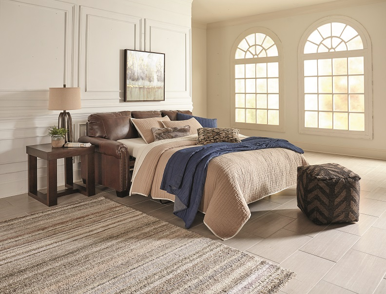 Sleeper sofa pulled out with blankets and pillows in a large room with windows.