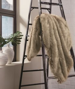Light brown faux fur throw blanket dangled over a ladder next to a window.