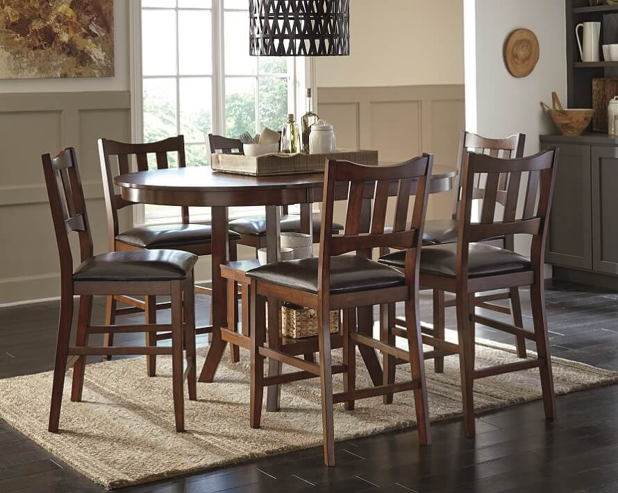 Brown oval dining table with brown wooden chairs and a neutral rug underneath.