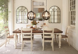 Farmhouse styled dining room with industrial lighting hanging above and two mirrors on the back wall.